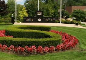 "Hedges trimmed in the shape of an ""S"" and surrounded by flowers in Shelby Township MI"